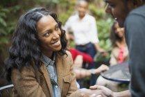Groupe de joyeux amis assis ensemble dans parc arboré et parler. — Photo de stock
