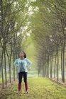 Mulher entre fileiras de árvores olhando para cima com as mãos nos quadris .. — Fotografia de Stock