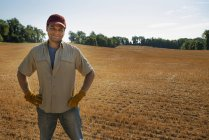 Man with hands on hips standing by freshly ploughed field. — Stock Photo