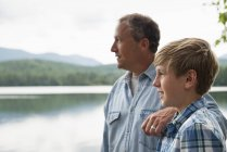 Отец и сын стоят на берегу озера и смотрят на него . — стоковое фото