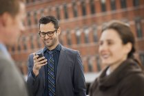 Mid adult businessman using smartphone with people talking in foreground. — Stock Photo