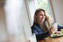 Junge Frau lächelt, während sie ihr Smartphone am Cafétisch mit Getränken und Essen benutzt. — Stockfoto