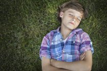 Overhead view of boy with arms folded lying on green grass with eyes closed. — Stock Photo