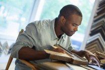Jovem segurando moldura de imagem e usando tablet digital na bancada no estúdio de moldura de imagem . — Fotografia de Stock