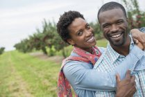 Couple hugging and smiling in camera at organic apple tree orchard. — Stock Photo