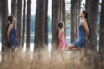 Três jovens mulheres encostadas a árvores em bosques com lago . — Fotografia de Stock