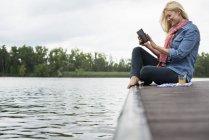 Vista laterale della donna seduta sul molo vicino al lago e utilizzando tablet digitale . — Foto stock