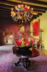 Zona de comedor con decoración de sandía en mesa y araña vintage - foto de stock