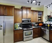 Cocina contemporánea con electrodomésticos y flores en casa de lujo - foto de stock
