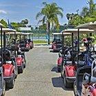 Parc de voiturettes de golf stationnées sur un terrain de golf tropical, Bradenton, Floride, États-Unis — Photo de stock