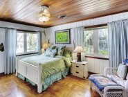 Спальня з дерев'яною стелею і затишним ліжком — стокове фото