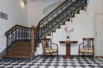 Escalier dans le hall élégant avec table et chaises — Photo de stock