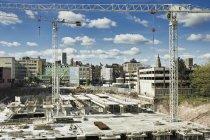 Краны над строительной площадкой и зданиями в сельской местности в Англии, Великобритании — стоковое фото