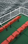 Orange chairs rows on green carpet on ferry, Ross-Shire, Scotland, UK — Stock Photo