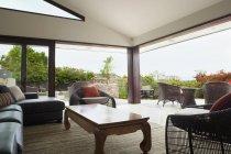 Modern living room overlooking patio with garden — Stock Photo