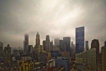 Arquitectura da cidade nevoenta com nuvens dramáticas sobre arranha-céus de New York City, New York, EUA — Fotografia de Stock