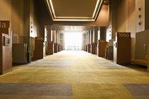Corredor en centro de conferencias con puertas numeradas y retroiluminadas - foto de stock
