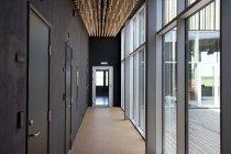 Moderno pasillo de oficina con grandes ventanales y pared con puertas - foto de stock