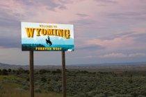 Cowboy on bucking bronco on Bienvenido a Wyoming signo, Wyoming, Estados Unidos - foto de stock