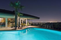 Illuminated pool at night with city in background, Los Angeles, California, United States — Stock Photo