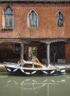 Bateau amarré par l'ancien bâtiment sur le canal à Venise, Italie, Europe — Photo de stock