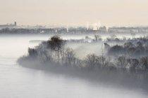 Niebla envuelta río y planta industrial en la distancia, Louisiana, EE.UU. - foto de stock