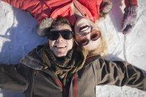 Casal jovem em óculos de sol sorrindo enquanto estava deitado na neve no inverno — Fotografia de Stock