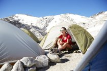 Female hiker sitting in tent at campsite — Stock Photo