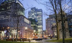 Park benches in city at night with illuminated skyscrapers on street of Montreal, Canada — Stock Photo