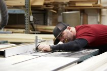 Carpenter using table saw in workshop interior — Stock Photo