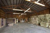 Feno fardos empilhados no interior do celeiro fazenda — Fotografia de Stock