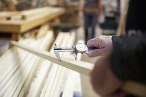 Плотник измеряет деревянную доску в мастерской — стоковое фото