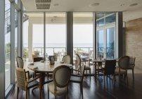 Tavoli vuoti in ristorante di lusso da pareti di vetro e finestre — Foto stock