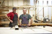 Два чоловічій теслярі посміхаються в інтер'єрі семінару — стокове фото