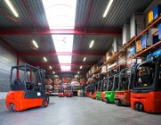 Forklift machinery parked in a row in warehouse — Stock Photo