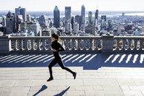 Mulher branca correndo na cidade com arranha-céus à distância, Montreal, Canadá — Fotografia de Stock