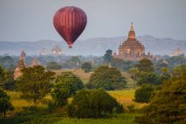 Hot air balloons flying over ancient stupa towers in Yangon, Myanmar, Asia — Stock Photo