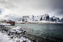 Montanhas nevadas com vista para a costa rochosa, Reine, Lofoten Islands, Noruega — Fotografia de Stock