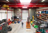 Vista turva do trabalhador caminhando no interior do armazém — Fotografia de Stock