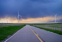 Wind turbines near road at sunset, Colorado, USA — Stock Photo
