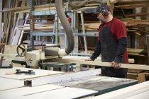 Carpenter using saw in workshop interior — Stock Photo