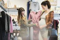 Mulher grávida caucasiana compras com amigo na loja de roupas — Fotografia de Stock