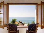 Порожні стільці перед відкритим вікном з видом на Тихий океан — стокове фото