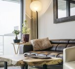 Sofa, potted plants and armchair near living room window — Stock Photo