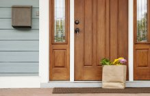 Grocery bag on front stoop of rural house — Stock Photo