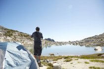 Man standing at tent at campsite near rural lake and watching grazing mountain goat — Stock Photo