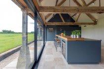 Barra do pequeno almoço e parede de vidro na cozinha moderna — Fotografia de Stock