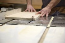 Hands of carpenter using table saw in workshop — Stock Photo