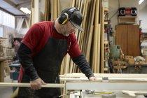 Плотник с помощью пилы в интерьере мастерской — стоковое фото