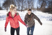 Young couple ice skating on frozen lake in winter — Stock Photo